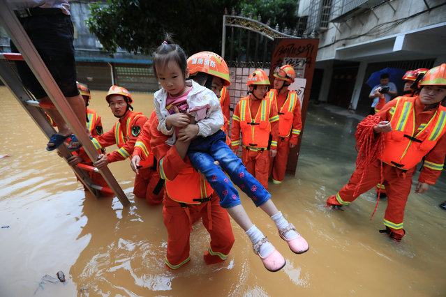 Chinese rescuers evacuate local residents in floodwater caused by a heavy rainstorm in Hengdong county, Hengyang city, east China's Hunan province on July 9, 2019. (Photo by Imaginechina/Shutterstock)