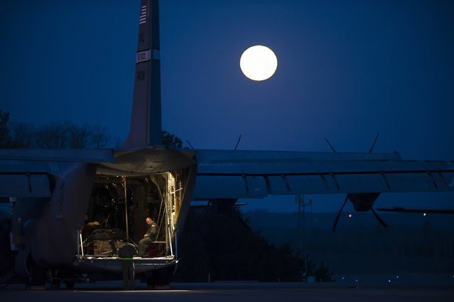 Airmen from the 19th Airlift Wing prepare a C-130J for a flight, beneath the light of a full moon on March 27, 2013, at Little Rock Air Force base in Arkansas. As home to the largest C-130 fleet in the world, the Little Rock base delivers mission-ready officers to fuel combat airlift operations. (Photo by Staff. Sgt. Russ Scalf)