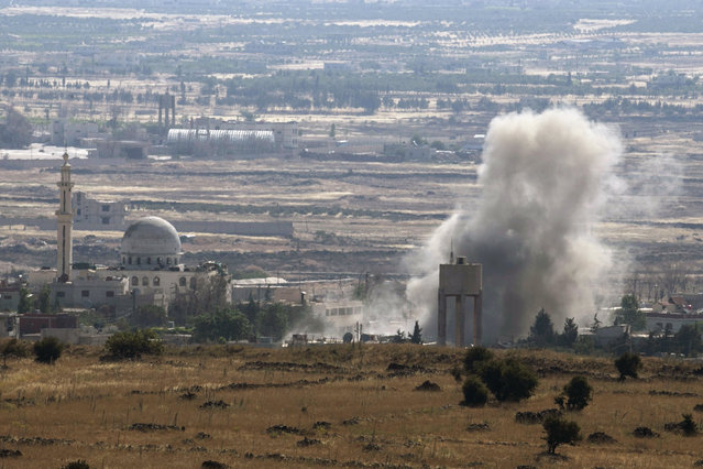 Smoke rises during fighting in the village of Ahmadiyah in Syria, as seen from the Israeli side of the border fence between Syria and the Israeli-occupied Golan Heights, June 17, 2015.  Israel signaled readiness on Tuesday to intervene if Syrian refugees were to throng to its armistice line on the Golan Heights, after Israel's Druze Arab minority stepped up a public campaign to help brethren caught up in the civil war next door. REUTERS/Baz Ratner TPX IMAGES OF THE DAY