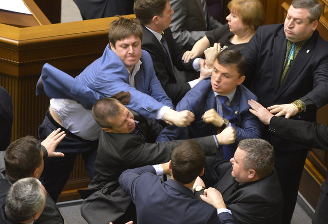 Communist lawmakers scuffle with right-wing Svoboda ( Freedom) Party lawmakers during a parliament session of Verkhovna Rada, the Ukrainian parliament, in Kiev, Ukraine Tuesday, April 8, 2014. (Photo by Vladimir Strumkovsky/AP Photo)