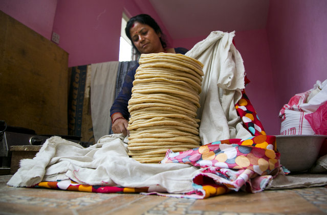 In this July 5, 2019, photo, Saraswati Dangol wraps rotisserie, or flat bread, after preparing them for monkeys near Pashupatinath temple in Kathmandu, Nepal. For the past four years, Dangol has been bringing the bread every day to feed some 300 monkeys. She buys some 10 kilograms (22 pounds) of flour and spends hours cooking the roti, traveling to the forest temple and feeding them daily. (Photo by Niranjan Shrestha/AP Photo)
