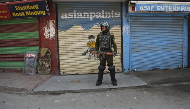 An Indian paramilitary soldier stands guard during restrictions imposed by government in Srinagar, Indian controlled Kashmir, Wednesday, April 27, 2016. Government forces Wednesday imposed vehicle traffic restrictions in some parts of valley after separatists in the Kashmir Valley called for mass funeral prayers for Jammu and Kashmir Liberation front or JKLF founder and supporter of armed struggle Amanullah Khan, 86, who died at a Rawalpindi hospital in Pakistan on Tuesday. (Photo by Mukhtar Khan/AP Photo)