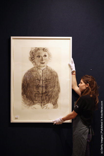 A gallery assistant adjusts a print of a David Hockney artwork entitled Soft Celia estimated to fetch 5,000 GBP in Bonhams auction house