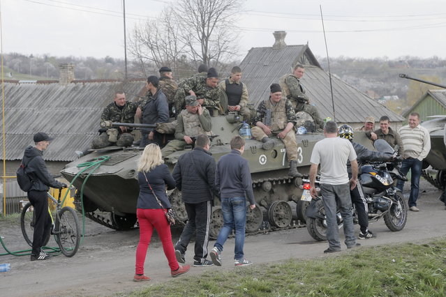Soldiers of the Ukrainian Army sit a top combat vehicles as they are blocked by people on their way to the town of Kramatorsk on Wednesday, April 16, 2014. The central government has so far been unable to rein in the insurgents, who it says are being stirred up by paid operatives from Russia and have seized numerous government facilities in at least nine eastern cities to press their demands for broader autonomy and closer ties with Russia. (Photo by Efrem Lukatsky/AP Photo)