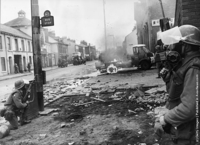 1970:  Armed British troops take up defensive positions on the Falls Road. 5 Catholics were killed, 60 injured and many homes devastated when the British Army imposed a curfew in the Falls Road