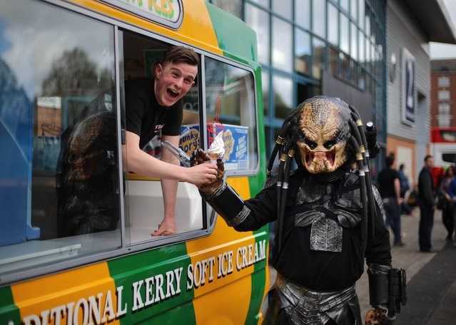 A man dressed in a costume from the movie Predator buys an ice cream at the MCM Ireland Comic Con at the RDS in Dublin, on April 13, 2014. (Photo by Niall Carson/PA Wire)