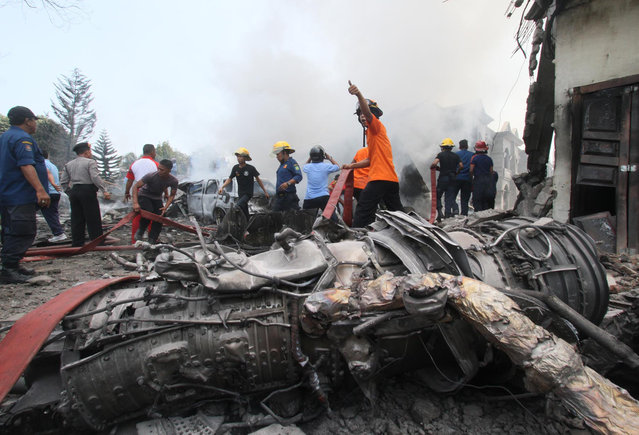 Firefighters and military personnel work at the site where an Air Force cargo plane crashed in Medan, North Sumatra, Indonesia, Tuesday, June 30, 2015. (Photo by Gilbert Manullang/AP Photo)