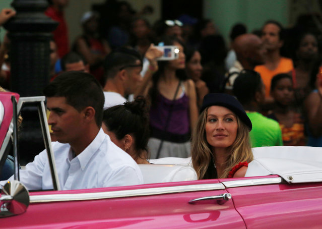 Brazilian supermodel Gisele Bundchen (R, blue hat) rides in a vintage car to attend a fashion show by Chanel, the first major fashion house to send models down the catwalk in Cuba, in Havana, May 3, 2016. (Photo by Reuters/Stringer)
