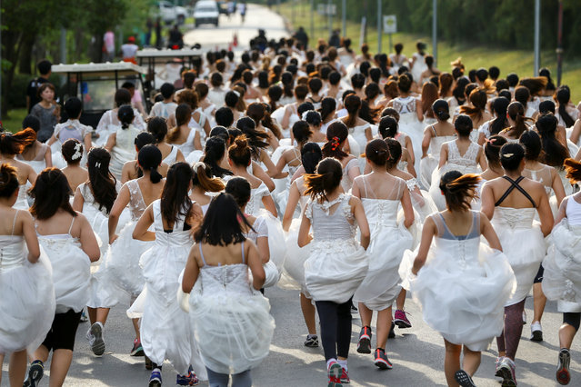 """Brides-to-be participate in the """"Running of the Brides"""" race in a park in Bangkok, Thailand March 25, 2017. (Photo by Athit Perawongmetha/Reuters)"""