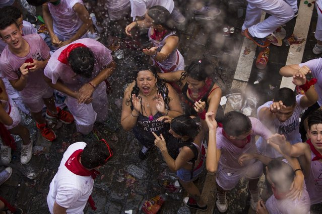 """Revelers celebrates as people throw water from the balconies during the launch of the """"Chupinazo"""" rocket, to celebrate the official opening of the 2015 San Fermin festival in Pamplona, Spain, Monday, July 6, 2015. (Photo by Andres Kudacki/AP Photo)"""