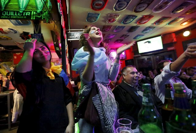 A fan supporting Argentina (C) celebrates as fans supporting Colombia react after penalties in their Copa America quarter-final soccer match, at a bar in Vina del Mar, Chile, June 26, 2015. Argentina advanced to the semi-finals of the Copa America 5-4 on penalties on Friday following a 0-0 draw with Colombia. (Photo by Henry Romero/Reuters)