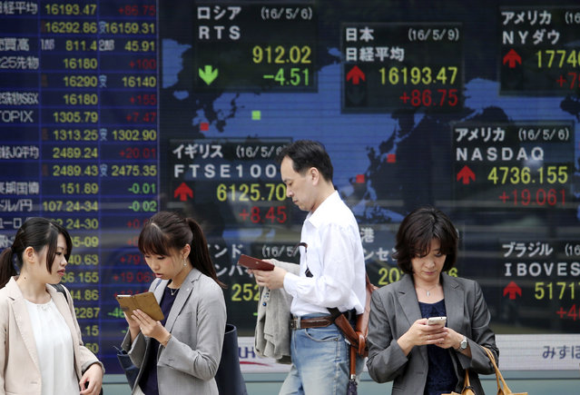 People stand in front of an electronic stock board of a securities firm in Tokyo, Monday, May 9, 2016. Asian stocks were mixed Monday after China's trade contracted in April and U.S. job growth came in weaker than expected. (Photo by Koji Sasahara/AP Photo)