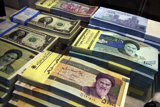 In this April 4, 2015 file photo, Iranian and U.S. banknotes are on display at a currency exchange shop in downtown Tehran, Iran. Iran's currency is continuing its downward spiral as increased American sanctions loom, hitting a new low on the thriving black market exchange. The Iranian rial fell to 112,000 to the dollar on Sunday, July 29, 2018, from 98,000 to $1 on Saturday. (Photo by Vahid Salemi/AP Photo)