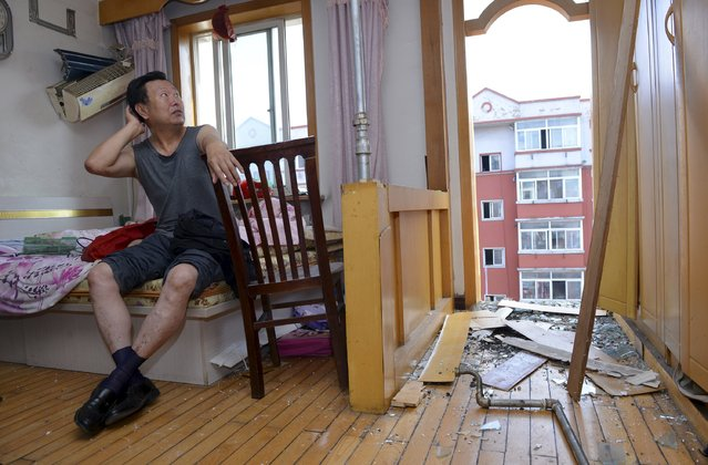 A man living on the sixth floor of an apartment building where the balconies of two units on the seventh and the sixth floor fell off, scratches his head as he looks at the damage, in Shenyang, Liaoning province, China, July 6, 2015. (Photo by Reuters/Stringer)