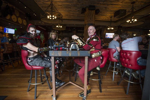 Cosplay enthusiasts John Callison (R), Bill Dorvall and his wife Vicki wear costumes as they sit at a restaurant during the 2015 Comic-Con International Convention in San Diego, California July 9, 2015. (Photo by Mario Anzuoni/Reuters)