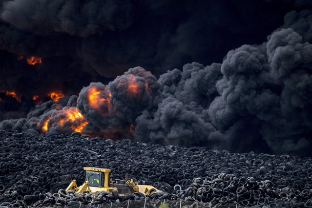 Flames rage through a pile of tires at the tire dump of Sesena in Toledo, Spain, 13 May 2016. The tire dump reportedly contains over 100,000 tons of tires and reaches to the neighbouring town of Valdemoro in Madrid. According to local authorities, the fire was apparently deliberately started as it had been raining till midnight and the fire started early 13 May 2016 at a small spot in Valdemoro. (Photo by Ismael Herrero/EPA)