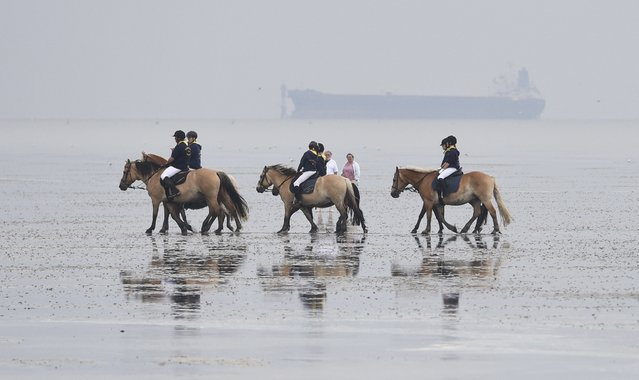 Jockeys ride horses on mud flats before their tideland race (Wadden Race) in Duhnen, Lower Saxony, Germany, July 12, 2015. (Photo by Fabian Bimmer/Reuters)