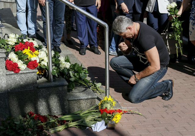 A man prays outside the Dutch embassy to commemorate the victims of the downing of Malaysia Airlines MH17 in eastern Ukraine a year ago, in Kiev, Ukraine July 17, 2015. (Photo by Gleb Garanich/Reuters)