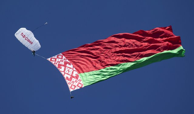 A parachutist with the Belarussian national flag is seen descending during an Air Sports Festival on the outskirts of Minsk, Belarus, July 18, 2015. (Photo by Vasily Fedosenko/Reuters)