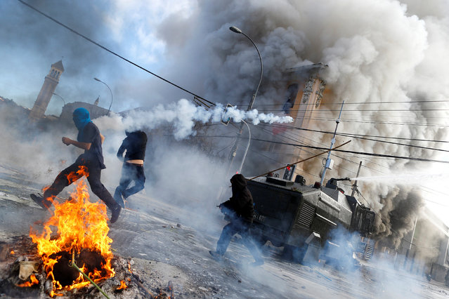 Anti-government demonstrators and riot police clash during a rally, as Chile's President Michelle Bachelet delivers a speech inside the National Congress, in Valparaiso city, Chile May 21, 2016. (Photo by Ivan Alvarado/Reuters)