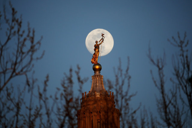 The moon rises behind a statue, known as Miss Penn or the Spirit of the Commonwealth, standing on the dome of the Pennsylvania State Capitol, Wednesday, April 20, 2016, in Harrisburg, Pa. (Photo by Julio Cortez/AP Photo)