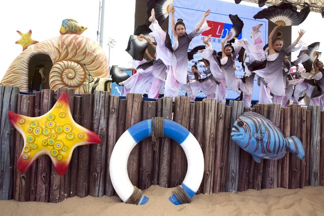 """Chinese performers take part in the opening of the """"Dreams of Europe and China"""" art exhibition at the Ocean Beach theme park in Beijing, China, Friday, July 10, 2015. The exhibition marks the 40th anniversary of official ties between the EU and China. (Photo by Ng Han Guan/AP Photo)"""