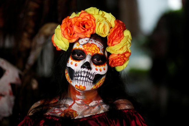 "A woman, painted as a Catrina, participates in a parade called ""La Calabiuza"" on the eve of the Day of the Dead in Tonacatepeque, El Salvador, November 1, 2019. (Photo by Jose Cabezas/Reuters)"