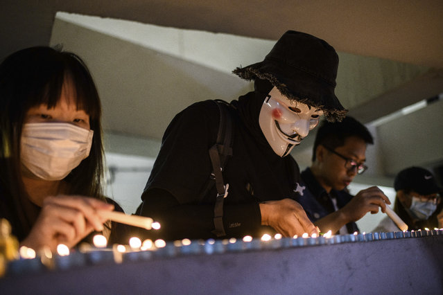 Mourners light candles as they pay their respects at the car park where student Alex Chow, 22, fell during a recent protest in the Tseung Kwan O area on the Kowloon side of Hong Kong on November 8, 2019. Thousands of Hong Kongers held vigils on November 8 night for a student who died from a fall during recent protester clashes with police, triggering fresh outrage from the pro-democracy movement and renewed violence. (Photo by Anthony Wallace/AFP Photo)