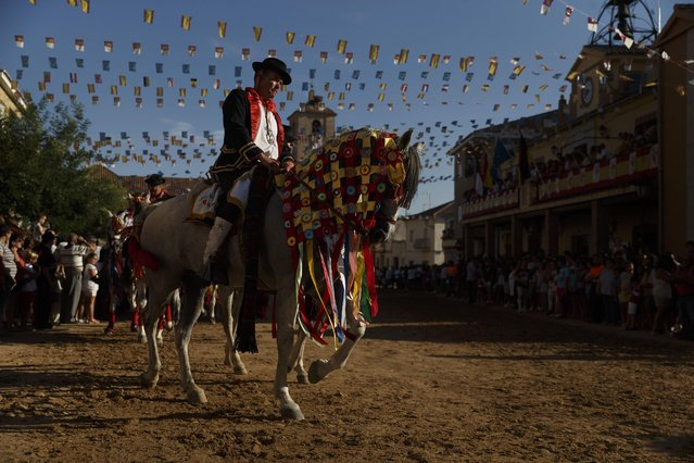 A rider on a horse back parades before ripping the head off a goose, hanging by its feet from a thick rope stretched across the town square, on the feast day of Santiago, the patron saint of Spain, during the ancestral festivities of Carpio de Tajo, central Spain, Saturday, July 25, 2015. (Photo by Daniel Ochoa de Olza/AP Photo)