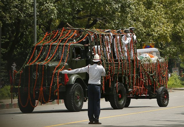 A traffic policeman directs the way for a vehicle carrying the body of former Indian President A. P. J. Abdul Kalam, wrapped with the national flag, outside Kalam's residence in New Delhi, India, July 28, 2015. Kalam, considered the father of the country's missile programme, died on Monday in hospital at the age of 83, a doctor said. (Photo by Anindito Mukherjee/Reuters)