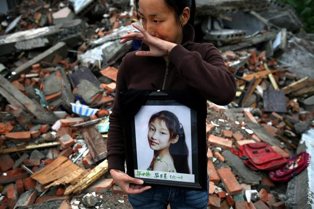 A mother cries as she holds a photo of his daughter who was killed in an earthquake, as she stands in the ruins of the Fuxin No.2 Primary School in Wufu, in China's southwest Sichuan province May 29, 2008