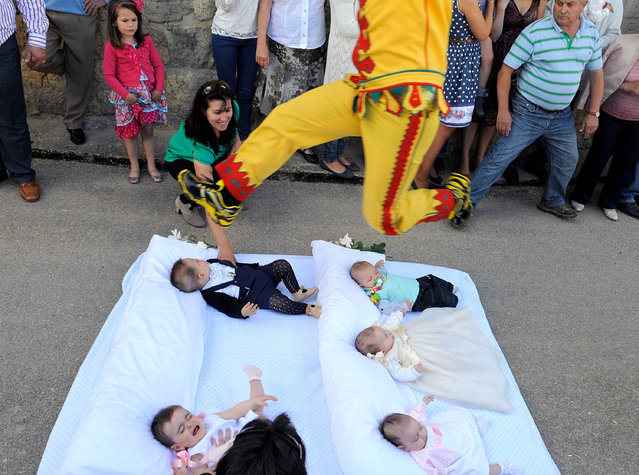 A man representing the devil leaps over babies during the festival of El Salto del Colacho (the devil's jump) on June 22, 2014 in Castrillo de Murcia, Spain. The festival, held on the first Sunday after Corpus Cristi, is a catholic rite of the devil cleansing babies of original sin. (Photo by Denis Doyle/Getty Images)