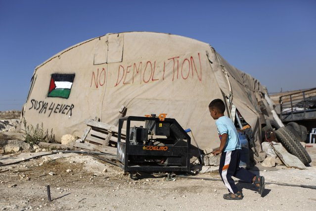 In this Tuesday, July 21, 2015, photo, a Palestinian boy runs outside his family tent in the village of Susiya, south of the West Bank city of Hebron. (Photo by Majdi Mohammed/AP Photo)