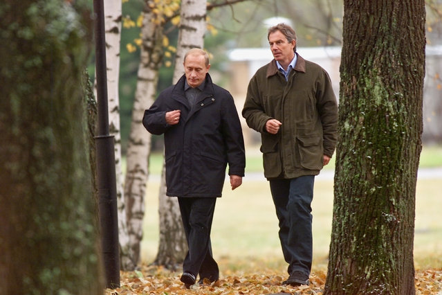British Prime Minister Tony Blair, right, and Russian President Vladimir Putin walk at a government residence in the region of Zavidovo, about 120 kilometers (75 miles) north of Moscow, Friday, October 11, 2002. Putin said Friday he believed the Security Council could reach common ground on Iraq and did not rule out Moscow's agreeing to a new U.N. resolution on the return of weapons inspectors to Iraq. (Photo by Alexander Zemlianichenko/AP Photo)