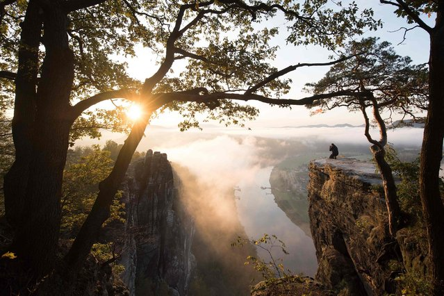 A man squats on the Bastei rock in the Saxon Switzerland National Park on October 7, 2019 and photographs the sunrise. (Photo by Sebastian Kahnert/dpa-Zentralbild/dpa via AFP Photo)