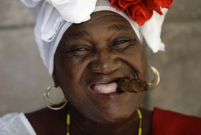 "Street entertainer and fortune teller ""Juana La Cubana"" smiles holding a cigar in her mouth as she waits for tourists in Havana, Cuba, Sunday, May 24, 2015. Juana is 72 years old and has worked in the Cathedral square in Old Havana for 28 years. (Photo by Desmond Boylan/AP Photo)"