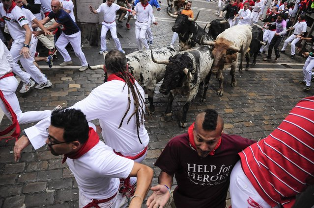 """Revelers run in front of """"Torrestrella"""" fighting bulls on Estafeta corner during the running of the bulls at the San Fermin festival, in Pamplona, Spain, Monday, July 7, 2014. (Photo by Alvaro Barrientos/AP Photo)"""