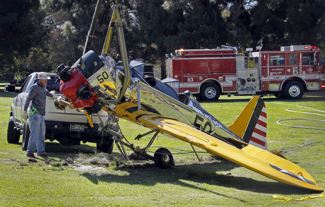 In this March 6, 2015, file photo, a World War II-era trainer airplane that actor Harrison Ford crash-landed Thursday, March 5 is removed from Penmar Golf Course in the Venice area of Los Angeles. Federal safety investigators have concluded that a problem with a carburetor part led to engine failure and the crash of a vintage airplane piloted by actor Harrison Ford in California. (Photo by Nick Ut/AP Photo)