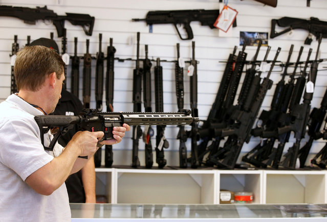 """A prospective buyer examines an AR-15 at the """"Ready Gunner"""" gun store in Provo, Utah, U.S., June 21, 2016. (Photo by George Frey/Reuters)"""