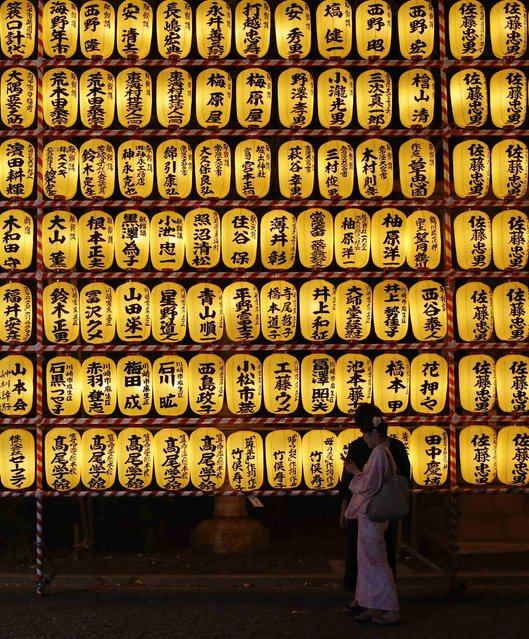 A couple in kimonos looks at pictures they took in front of paper lanterns during the annual Mitama Festival at the Yasukuni Shrine in Tokyo July 13, 2014. Over 30,000 lanterns light up the precincts of the shrine, where more than 2.4 million war dead are enshrined, during the four-day festival. The festival goes on till July 16. (Photo by Yuya Shino/Reuters)