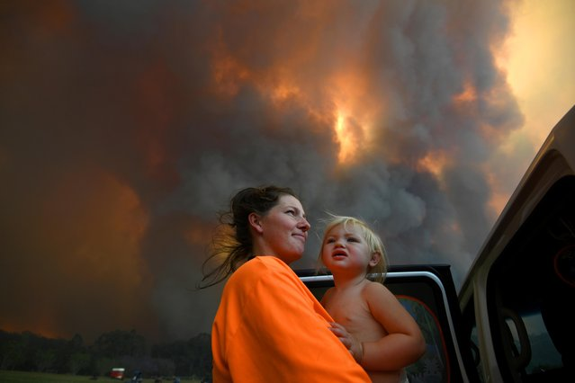 Sharnie Moren and her 18-month-old daughter Charlotte look on as thick smoke rises from bushfires near Nana Glen, near Coffs Harbour, Australia on November 12, 2019. There are more than 50 fires burning around the state of New South Wales, with about half of those uncontained. (Photo by Dan Peled/AAP Image via Reuters)