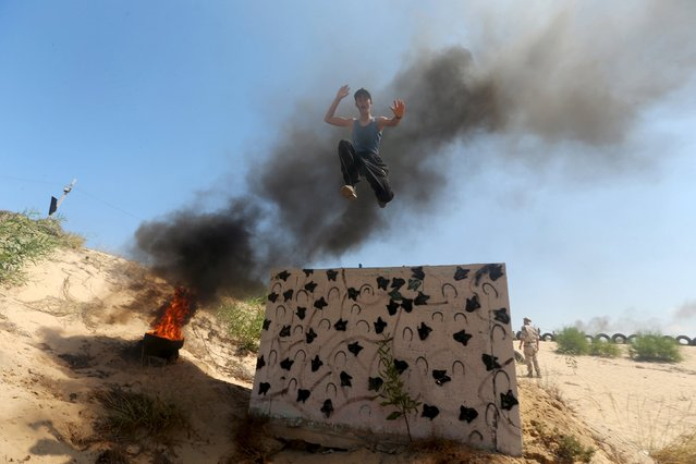 A young Palestinian jumps from the top of a wall during a military-style exercise at a summer camp organized by Islamic Jihad movement, in Khan Younis in the southern Gaza Strip, August 13, 2015. (Photo by Ibraheem Abu Mustafa/Reuters)