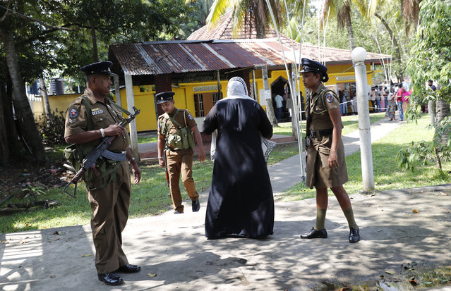 Sri Lankan police officers stand guard at a polling station as people queue to cast their votes during the presidential election in Colombo, Sri Lanka, Saturday, November 16, 2019. Polls opened in Sri Lanka's presidential election Saturday after weeks of campaigning that largely focused on national security and religious extremism in the backdrop of the deadly Islamic State-inspired suicide bomb attacks on Easter Sunday. (Photo by Eranga Jayawardena/AP Photo)