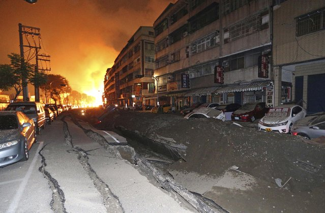 Tossed vehicles line an destroyed street as flames continue to burn from multiple explosions from an underground gas leak in Kaohsiung, Taiwan, early Friday, Aug. 1, 2014. A massive gas leakage early Friday caused five explosions that killed several people and injured over 200 in the southern Taiwan port city of Kaohsiung. (Photo by AP Photo)