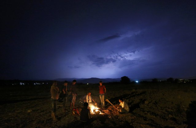A group of Syrian refugees gather around an open fire as a storm is approaching at a field at the Greek-Macedonian border, near the village of Idomeni, August 21, 2015. Macedonian police fired tear gas and stun grenades to drive migrants and refugees back from its southern border from Greece on Friday but crowds continued to build up at a new bottleneck in an increasingly desperate flight to western Europe. (Photo by Yannis Behrakis/Reuters)