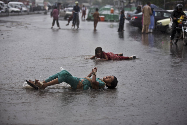 Pakistani girls who sell sweets to worshippers at a shrine, enjoy rolling on a flooded street during a sudden heavy rain fall after days of scorching temperatures due to a heat wave, in Islamabad, Pakistan, Thursday, August 7, 2014. (Photo by Muhammed Muheisen/AP Photo)