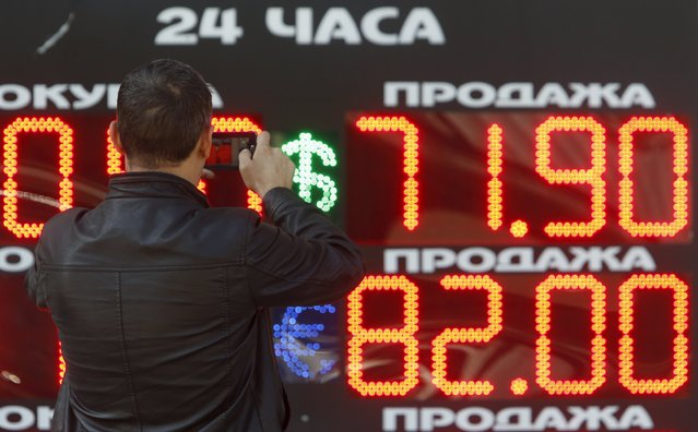 A man takes a picture of a board showing currency exchange rates of the U.S. dollar and euro (top-bottom) against Russian rouble in Moscow, Russia, August 24, 2015. (Photo by Sergei Karpukhin/Reuters)