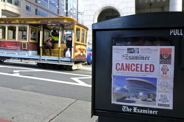 A newspaper headline announcing the closure of large events is displayed as a cable car goes down California Street, Friday, March 13, 2020, in San Francisco. A wave of closures and postponements spanning everything from government offices to cultural events and sports followed California Gov. Gavin Newsom's call this week for cancellation of all non-essential gatherings of 250 people or more because of the coronavirus threat. (Photo by Eric Risberg/AP Photo)