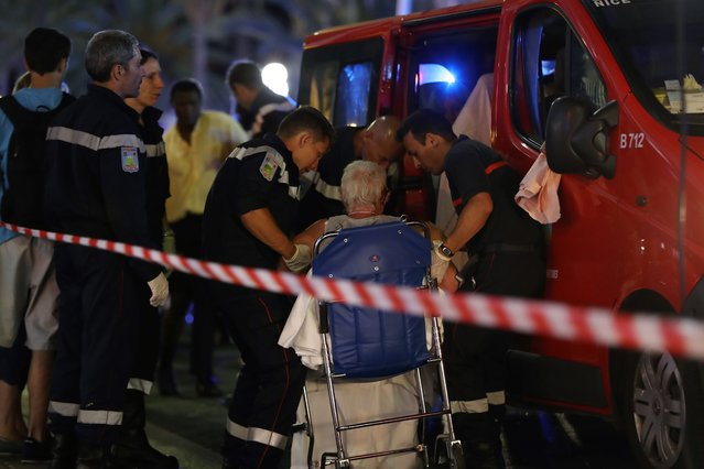 """Rescue workers help an injured woman to get in a ambulance on July 15, 2016, after a truck drove into a crowd watching a fireworks display in the French Riviera town of Nice. A truck ploughed into a crowd in the French resort of Nice on July 14, leaving at least 60 dead and scores injured in an """"attack"""" after a Bastille Day fireworks display, prosecutors said on July 15. (Photo by Valery Hache/AFP Photo)"""
