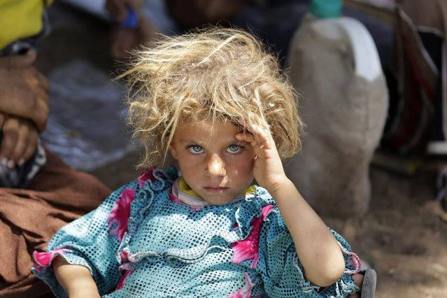 A girl from the minority Yazidi sect, fleeing the violence in the Iraqi town of Sinjar, rests at the Iraqi-Syrian border crossing in Fishkhabour, Dohuk province August 13, 2014. (Photo by Youssef Boudlal/Reuters)